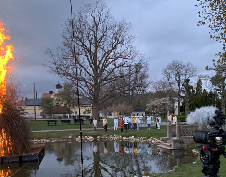 Valborgsbrasa på en liten flotte i en damm filmas av filmteam