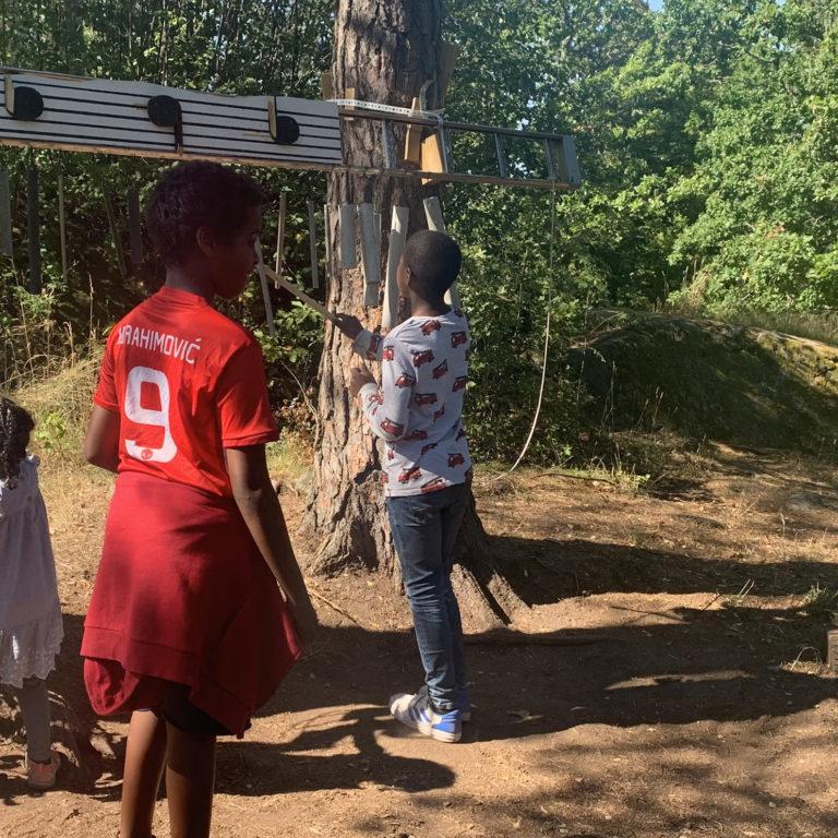 Barn i färgglada kläder leker med instrument i skogen.