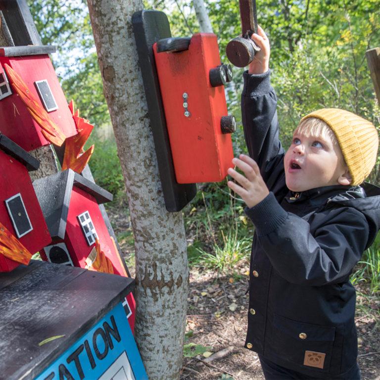 Barn i gul mössa låtsas ringa brandkåren med en leksakstelefon i trä