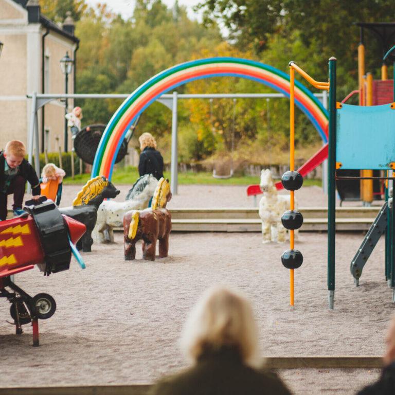 Barn leker på en lekplats där det finns lekställning, flygplan och gungor