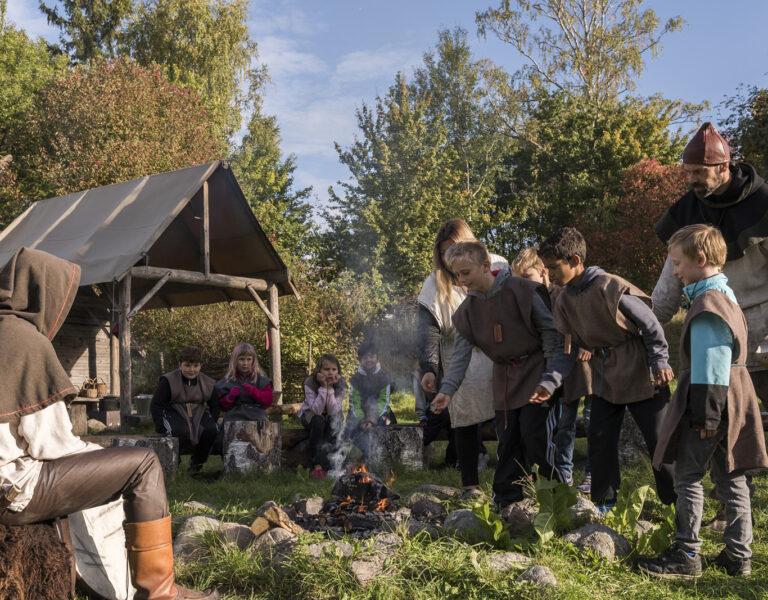 Barn och vuxna i bruna gammaldags kläder testar på järnåldersliv