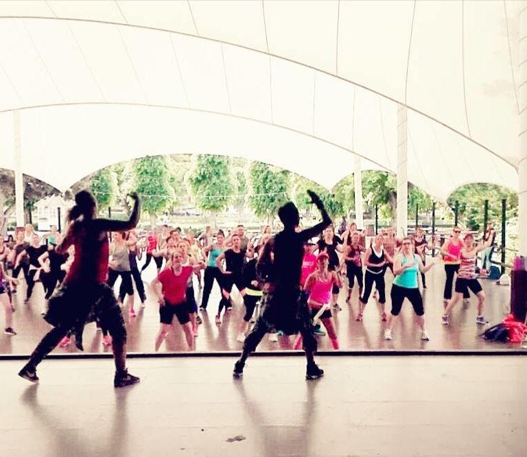 Dansinstruktörer dansar zumba på en scen med många deltagare framför sig