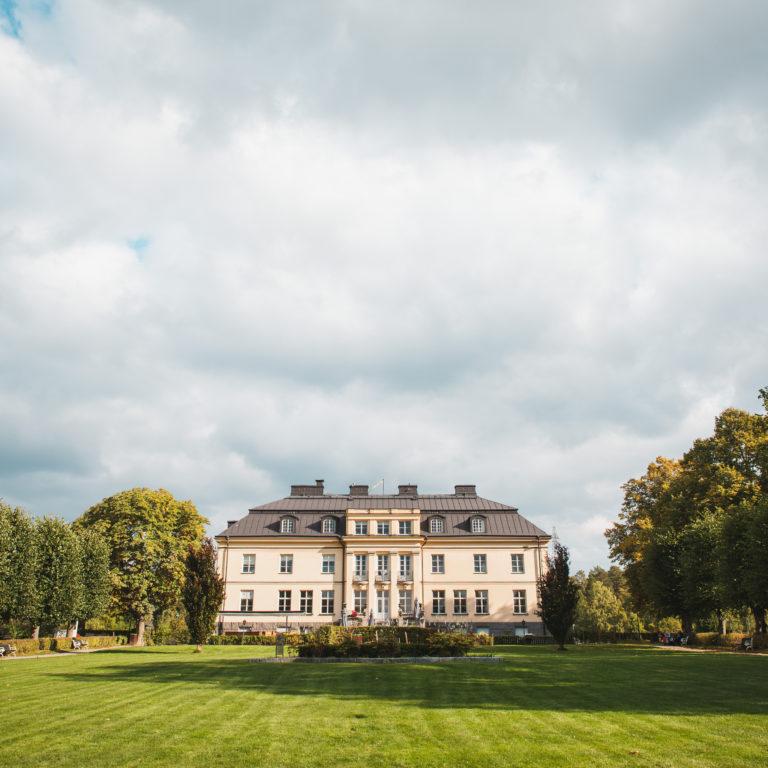 Huvudbyggnaden, herrgården, i Hågelbyparken en vacker molnig dag