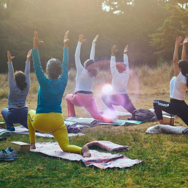 Personer utövaer yoga på en gräsmatta en solig morgon