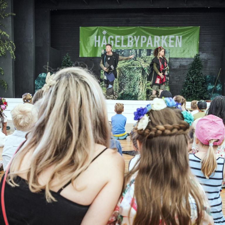 Publik med barn och vuxna tittar på barnteater utomhus
