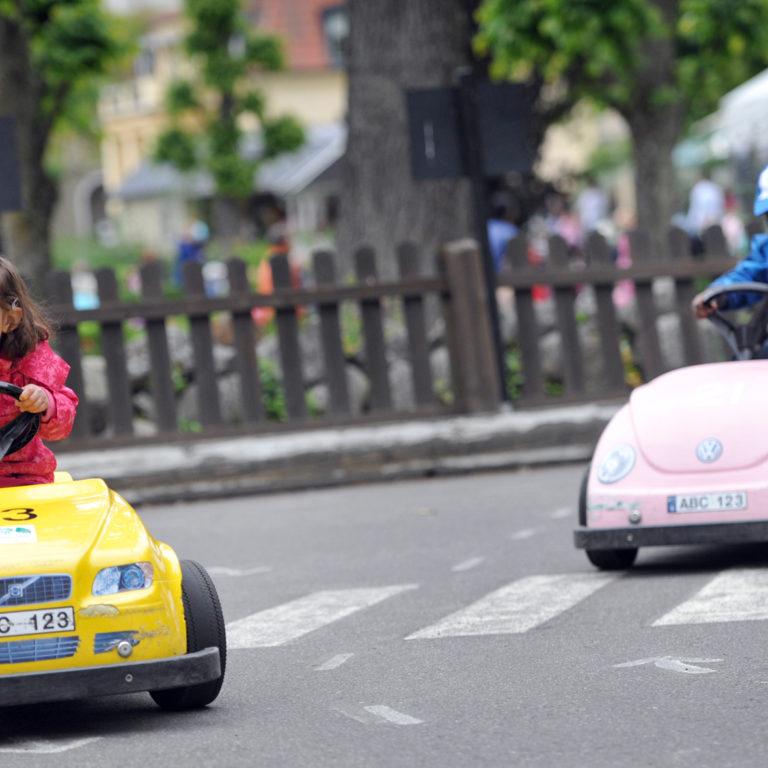 Barn som kör färgglada bilar på en trafiklek