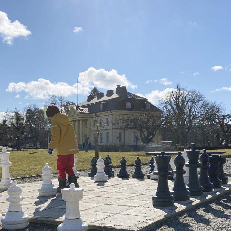 Barn och mamma spelar schack en solig vårvinterdag