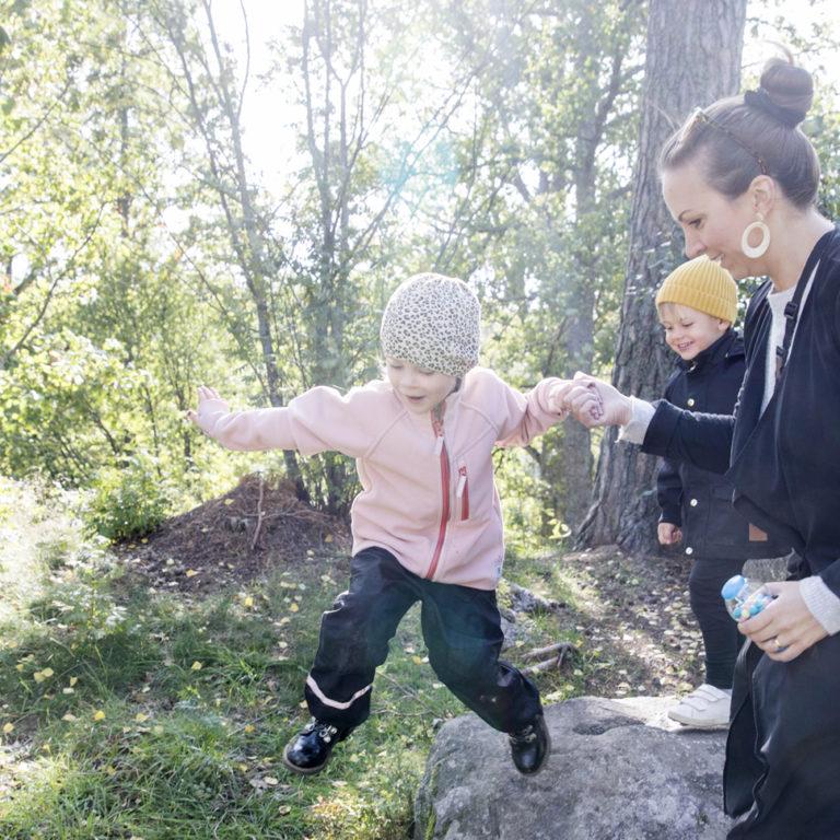 Barn och mammor hoppar och leker längs en stig i skogen