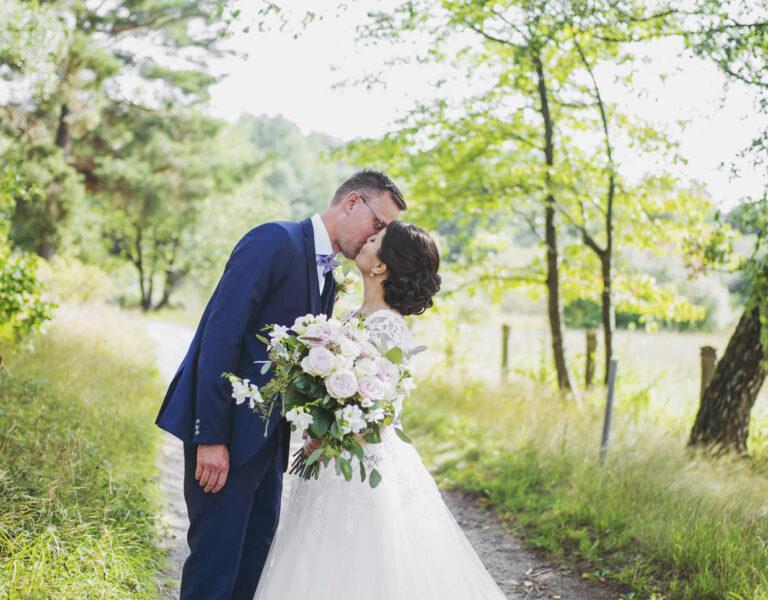 Bröllopspar kysser varandra på en stig i Hågelbyparken