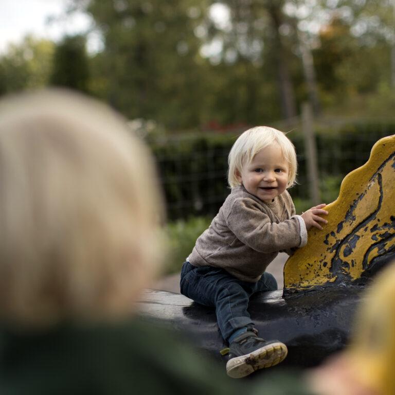 Litet glatt barn i beige tröja och blå byxor sitter på en hästskulptur