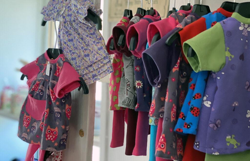 Färgglada dockkläder hänger på galgar