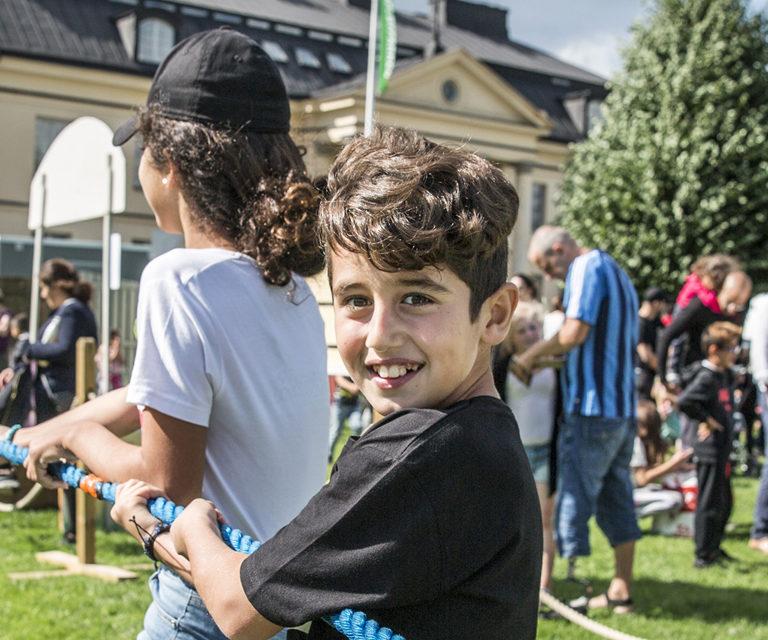Glada barn leker dragkamp på en gräsmatta
