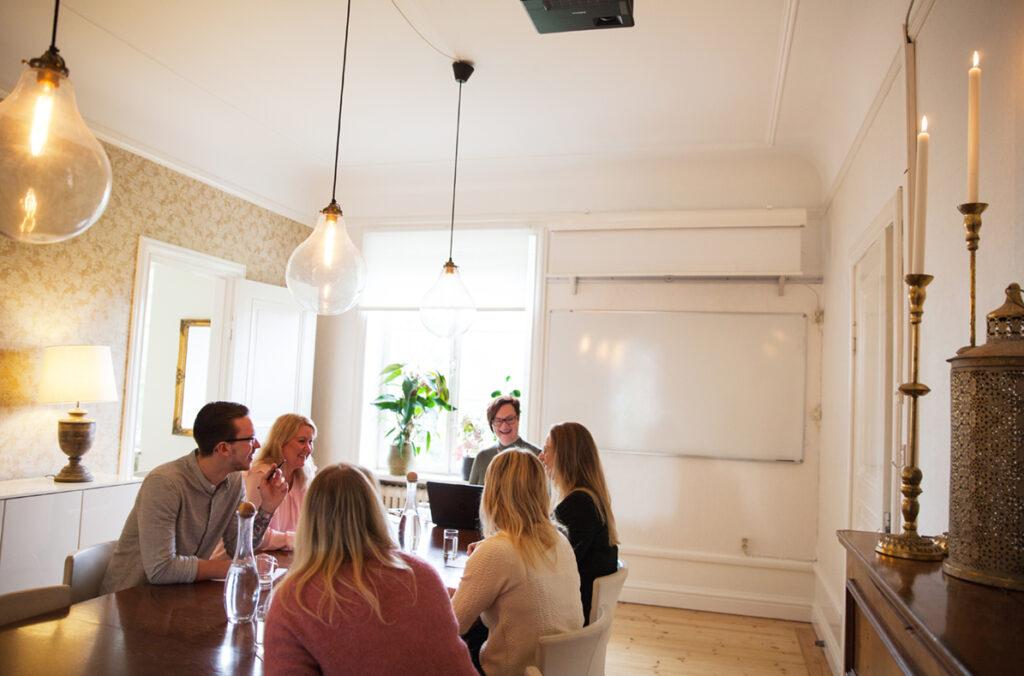 Sex glada konferensgäster sitter och samtalar i ett ljust konferensrum