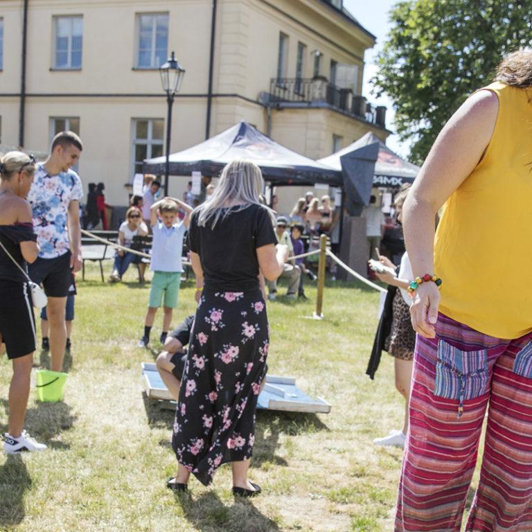 Glad kvinna försöker gå balansgång, mycket folk på gräsmattan bakom henne