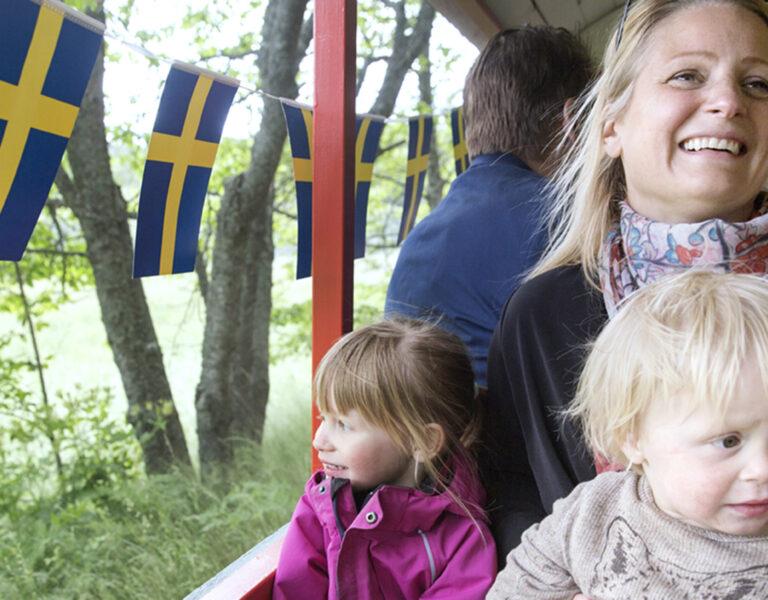 Glad kvinna åker tufftuff-tåg med två barn
