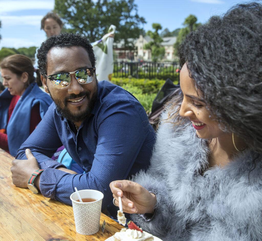 Leende man och kvinna sitter ute i solen och fikar