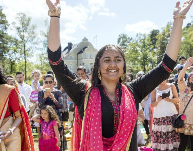 Leende och dansande kvinnor i färgglada indiska kläder