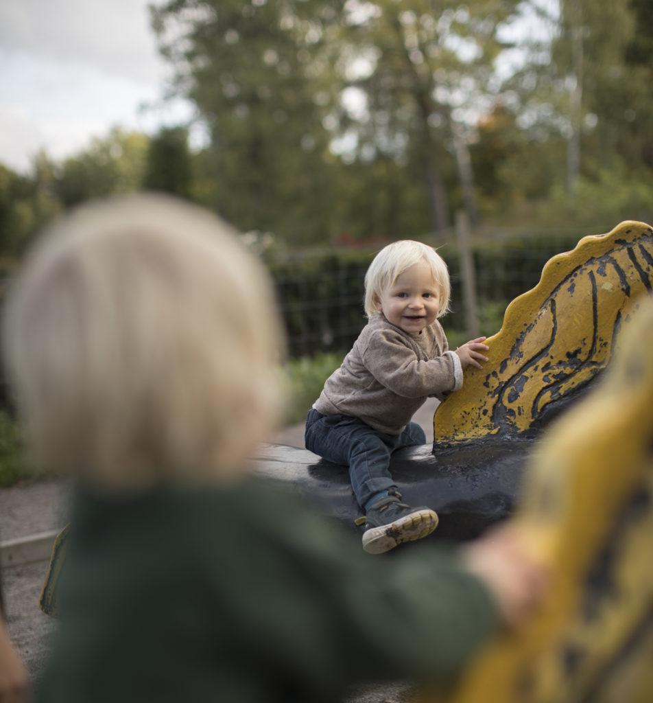 Glada små barn som leker på trähästar utomhus