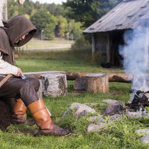 Man i bruna kläder sitter utomhus och arbetar med sin yxa