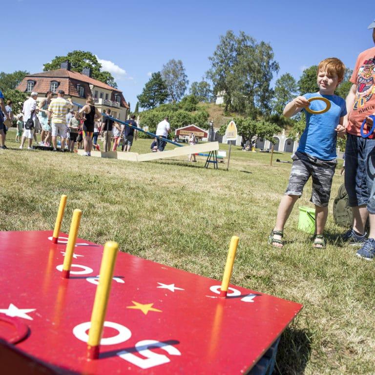 En klarblå sommar, pappa och barn spelar spel utomhus på en gräsmatta