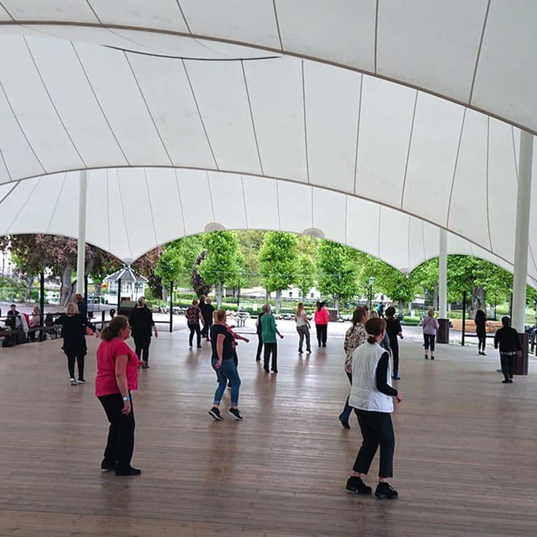 Personer dansar linedance på dansbana utomhus.