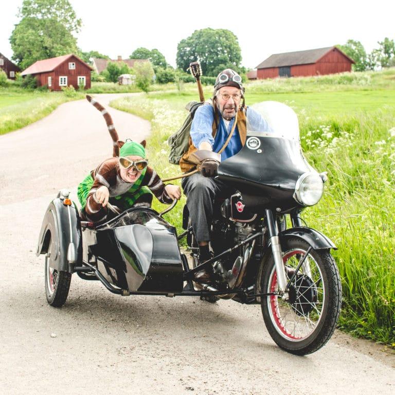 Pettsson och katten Findus åker motorcykel på en grusväg