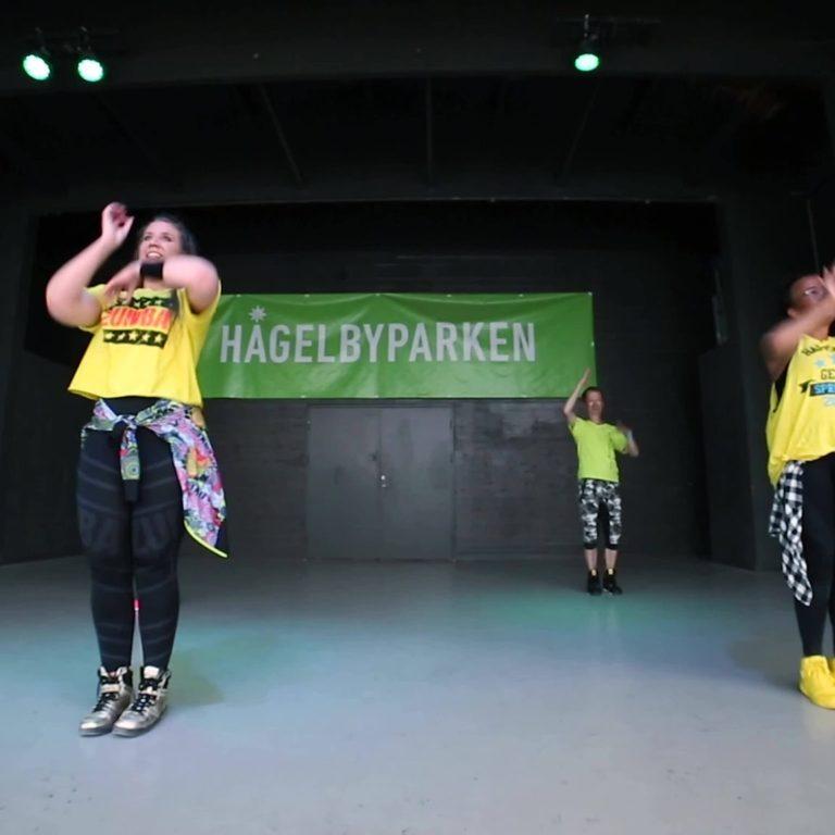 Personer i gula t-shirts dansar zumba på en scen