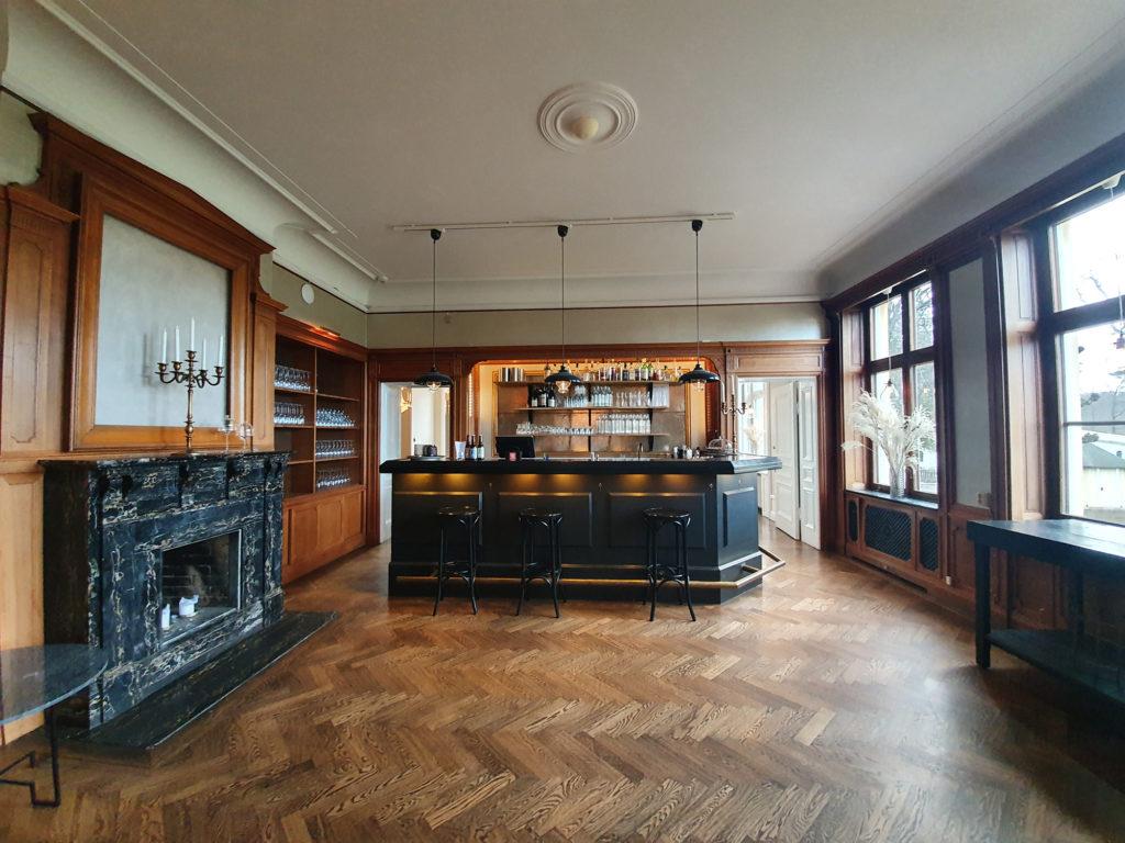 Rum med svart bardisk och mörk träpanel på väggarna