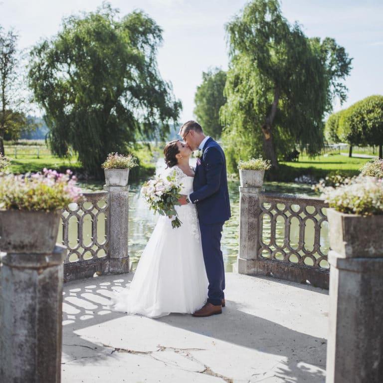 Bröllopspar som kysser varandra med en sjö i bakgrunden
