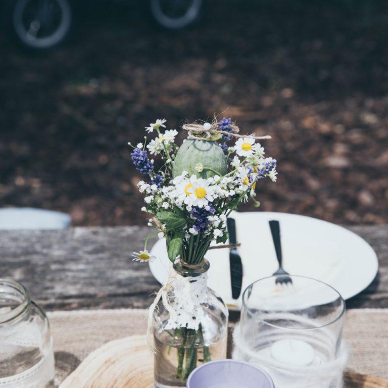 Dukning med sommarblommor i en vas
